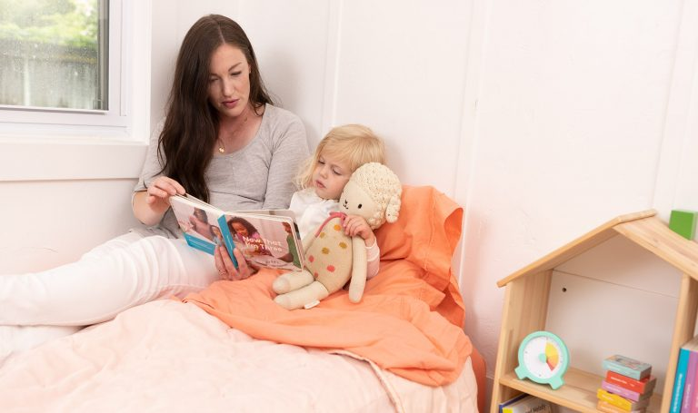 Mother reads to her child in bed.