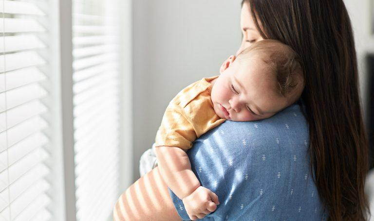 Mother cradles her sleeping baby.