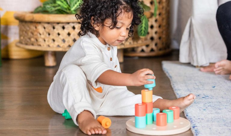 Child plays with stacking rings